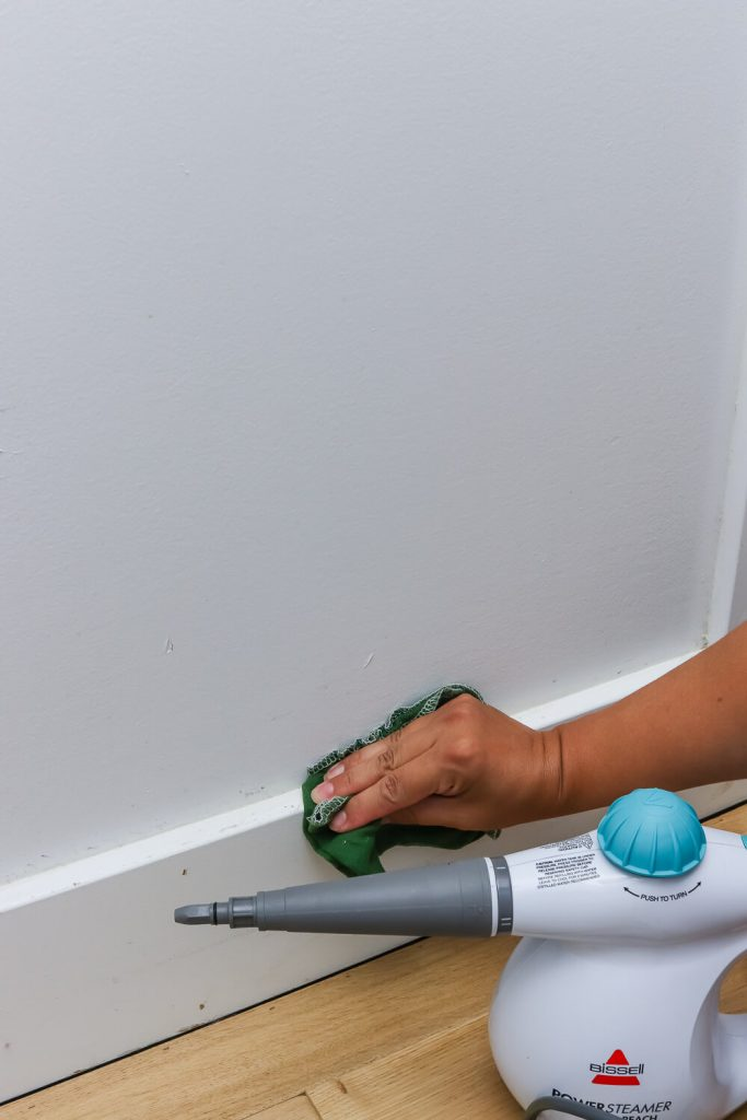 woman's hand using green cloth to wipe off baseboards