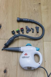 Bissell power steamer with extension hose with 6 attachments laying on wood floors