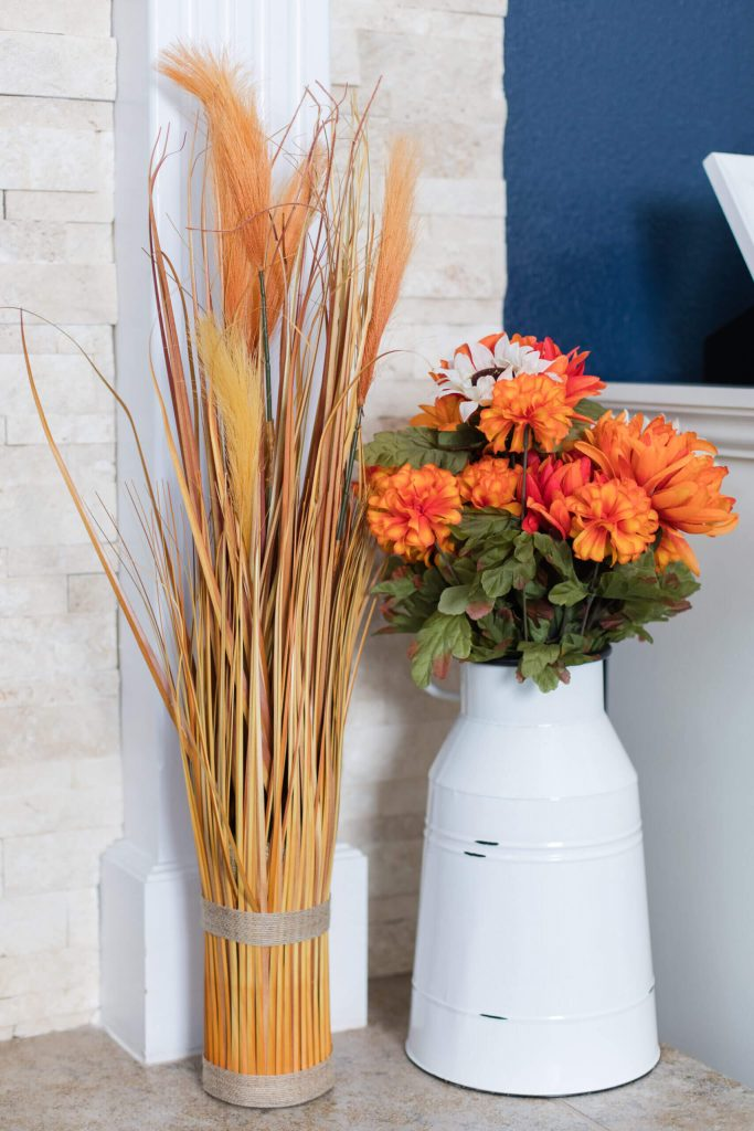 orange flowers in white vase with pampas grass beside it
