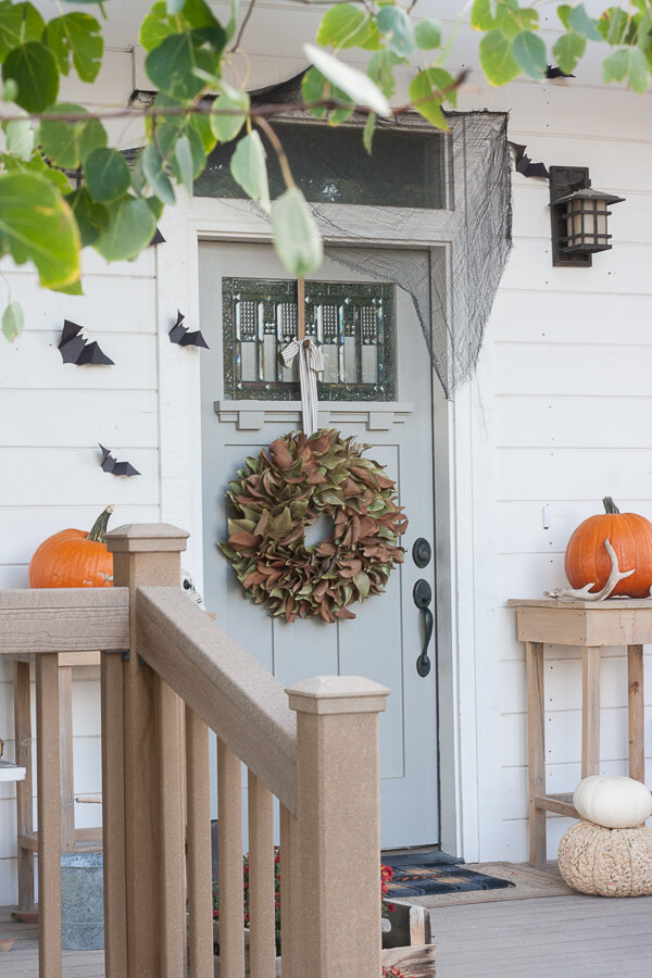 front porch with blue door and black bats decorated for fall and Halloween